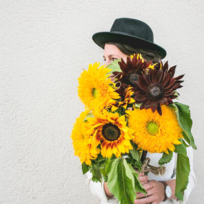 chica con girasoles de color amarillo y marron